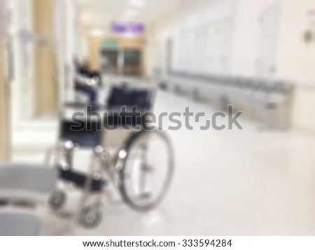 Blurred abstract background of hospital interior waiting hall/ corridor with wheelchair in front of nurse station and OPD - out patient clinic department: blurry view of walk way in clinical space    - stock photo