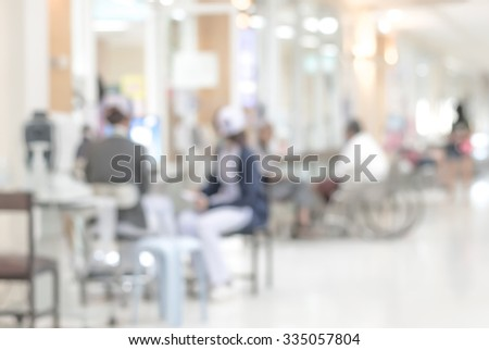 Blurred abstract background of hospital interior with nurses working in front of OPD - outpatient clinic department in waiting hall area for checking patients' health before seeing doctors - stock photo