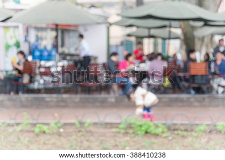 Blurred abstract background of kid playing in the garden of an outdoor cafe on the lakeside of Hoan Kiem Lake (Returned Sword Lake) in Hanoi.Outdoor cafe with outside tables, chairs, and umbrellas.