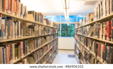Blurred abstract background of modern public library interior with aisle of bookshelf with textbooks, literature, thesis, magazines. Self-study, educational concept background. Panorama style.