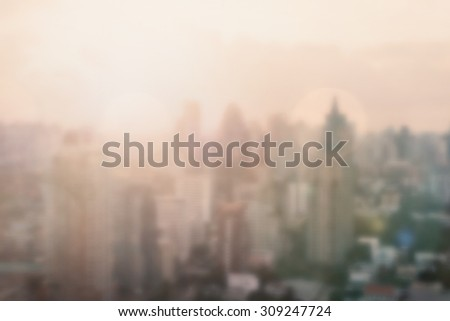Blurred abstract background of morning light rooftop view of downtown Bangkok urban skyline with sun flare and bokeh in vintage color tone: Blurry holiday city travel backgrounds of bright sunrise  - stock photo
