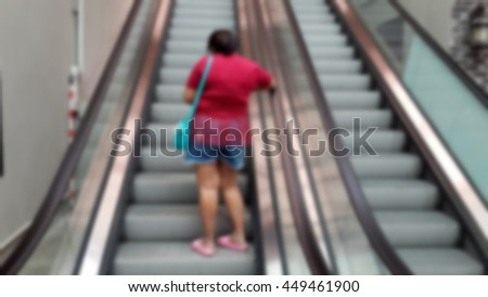 Blurred abstract background of people on escalator - stock photo