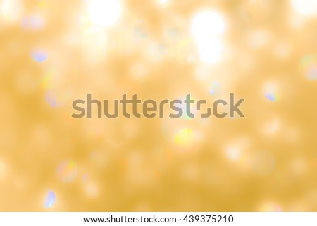 Blurred abstract background of reflective yellow gold magical bokeh of crystal mobile chandelier lamp bright golden color lighting vintage tone: Festive holiday shiny sparkling glass reflection light - stock photo