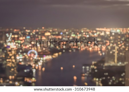 Blurred abstract background of rooftop view of city night lights bokeh in warm gold vintage color tone: Blurry perspective aerial view of hotel/ office building/ cbd central business district  - stock photo