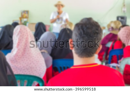 Blurred abstract background of university students sitting in a lecture room with teacher of the out Community education
