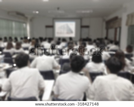 Blurred abstract background of university undergraduate students studying in a classroom: Blurry view of college school class from back of the lecture room with projector screen in from of the class - stock photo