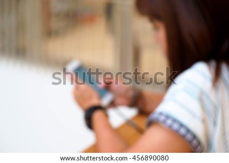 Blurred abstract background of Woman using a smart phone.