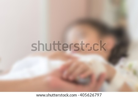 Blurred abstract background of young Asian girl kid patient sleeping recovery in hospital bed in ward room with family caregiver/ nurse supportive helping hand support: Nursing caretaker concept