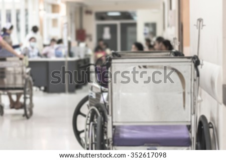 Blurred abstract background rear view of wheelchair for disabled person in hospital hallway  at outpatient department clinic-OPD with patient waiting to see doctor waiting/ queuing near nurse station  - stock photo