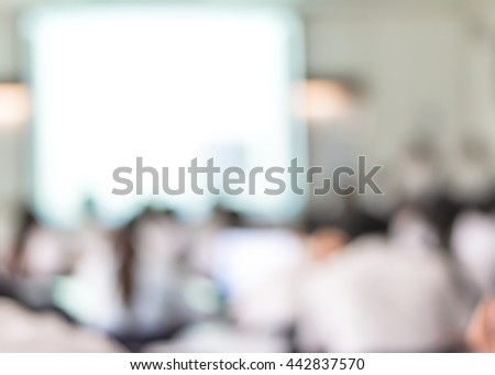 Blurred abstract background university students sitting in lecture room with lecturer in front of class with white projector slide screen: Blurry view from back of classroom presentation: Teachers day - stock photo