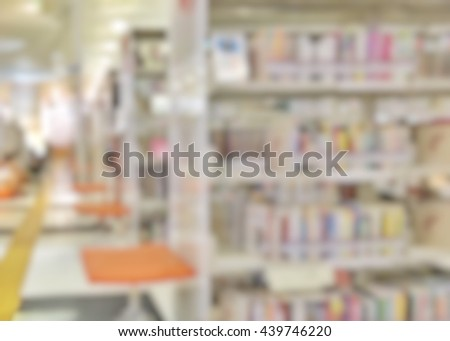 Blurred abstract background view of book shelves in public school library with people student behind aisle : Blurry interior perspective study room with table desks, chairs, seats & stacks of books   - stock photo