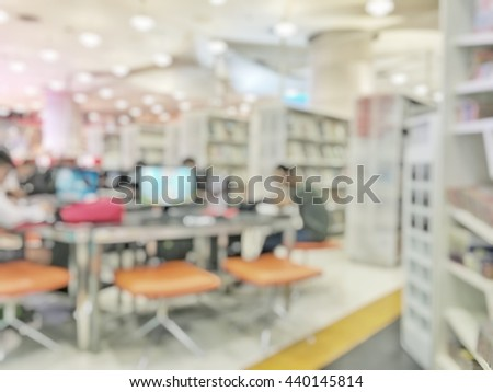 Blurred abstract background view of book shelves in public school library with people student among aisle: Blurry interior perspective computer study room with table desks, chairs, seats, book stacks  - stock photo