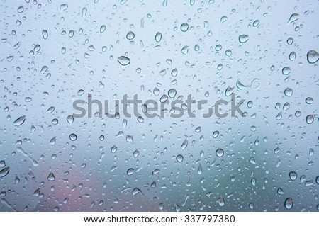 Blurred abstract background view of Rain drops on window surface with Boke Bowl, soft focus city view background - stock photo
