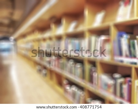 Blurred abstract background view of university/ school public library aisle of book shelves no student: Blurry interior perspective indoor study room with tables, chairs, seats & stacks of books  - stock photo
