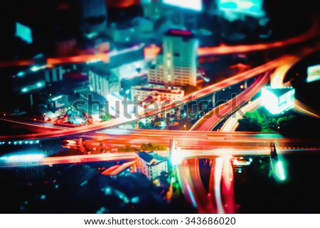 Blurred abstract futuristic night cityscape aerial view panorama with illuminated skyscrapers and city traffic across streets. Bangkok, Thailand - stock photo