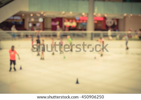 Blurred abstract motion background of parents and kids play indoor ice skating in modern shopping mall. Defocused of indoor ice skating with people on ice rink. Natural light from glass roof. Vintage. - stock photo