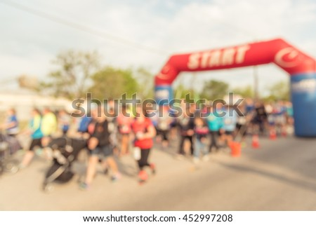 Blurred abstract motion group runners at starting line of 10K race in Katy, Texas, US. Fitness and healthy lifestyle concept. People competing in Marathon.Athletes at start line of race.Vintage filter - stock photo