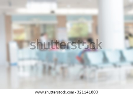 Blurred abstract of indoor waiting hall in hospital lobby in front of cashier and pharmacy dispensary counter with patients and nurses in the area: Blurry bright view of healthcare clinic seating zone - stock photo
