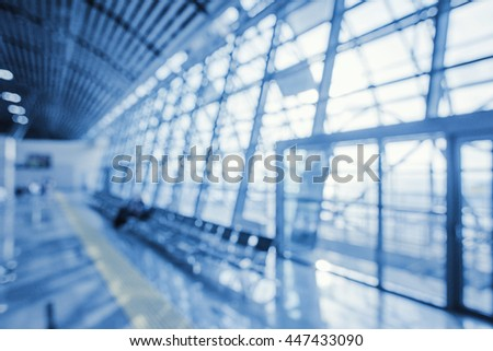Blurred airport terminal background. Airport or railway hall interior in bokeh. International gate, business trip, arrival or mall. Urban construction. - stock photo