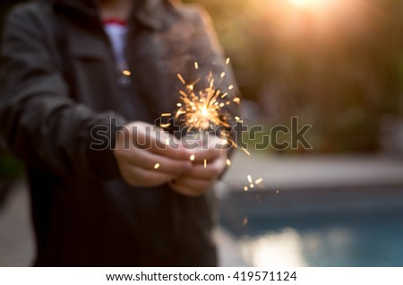Blurred and soft Concept hand holding sparkler with swimming pool sunset light in background - stock photo