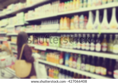 blurred asian woman choosing goods on shelves in supermarket:blur people buyer checking price in local market on weekend concept:blur girl shopping at market store center:vintage filter effect picture - stock photo