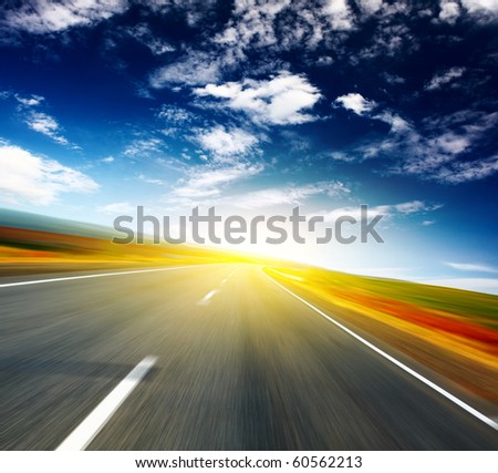 Blurred asphalt road and blue sky with clouds and light spot - stock photo