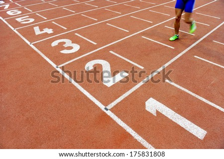 Blurred athlete by a slow camera shutter speed crossing the finish line after sprint track - stock photo