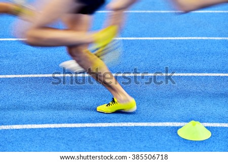 Blurred athletes by a slow camera shutter speed competing on blue sprint track - stock photo