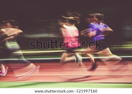 blurred athletes on running track - athletics concept