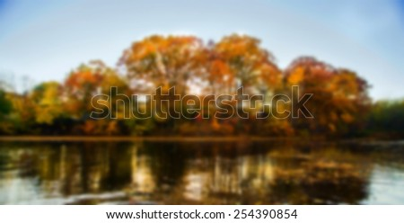 Blurred autumn landscape with water and colorful trees. - stock photo