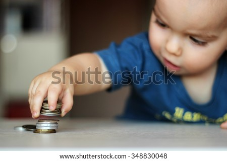 Blurred baby boy putting some coins into other ones, focus on the coins, indoor financial concept - stock photo
