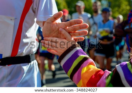 Blurred backgriund: marathon running race, support runners on road, child's hand giving highfive, sport concept