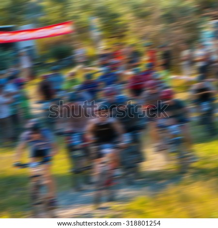 blurred background, a group of sporting cyclists riding on rough terrain