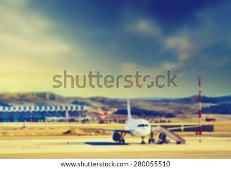 Blurred background : Airplane at the terminal gate Modern international airport at sunset. Vintage picture. Business and Travel concept - stock photo