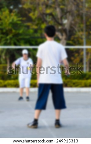 blurred background : boy and girl playing badminton