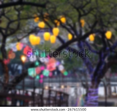 Blurred background created by colorful lantern hanging from trees and light up the river embankment  - stock photo