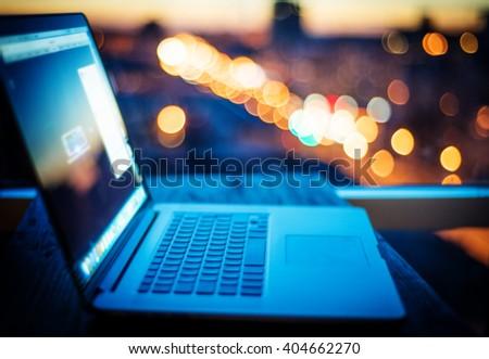 Blurred background : laptop on city night light background. - stock photo