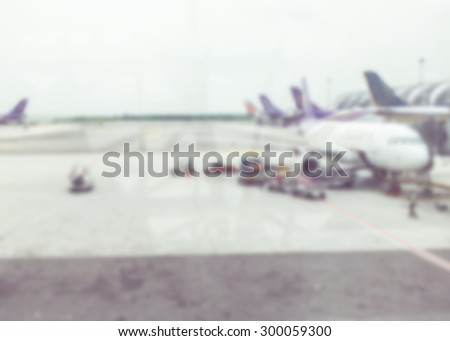Blurred background : looking through terminal window to see airplane at airport. - stock photo