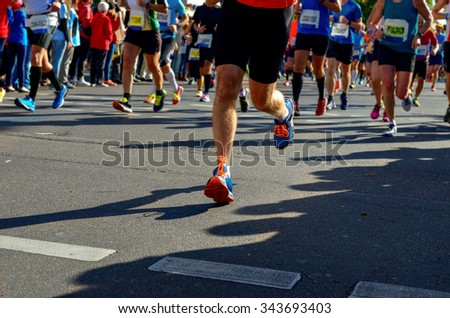 Blurred background: marathon running race, runners on road, sport, fitness and healthy lifestyle concept