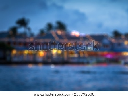 Blurred background of a restaurant on water, night view with bokeh lights - stock photo