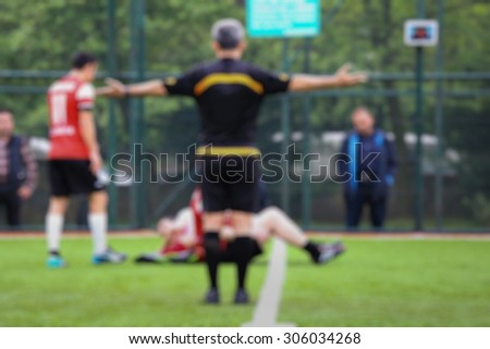 Blurred background of a soccer referee decides fault with his arms open.