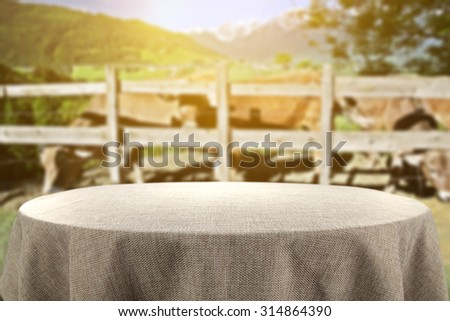 blurred background of alps and brown cows with big retro table of gray color  - stock photo