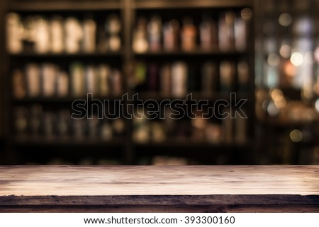 blurred background of bar and dark brown desk space of retro wood - stock photo