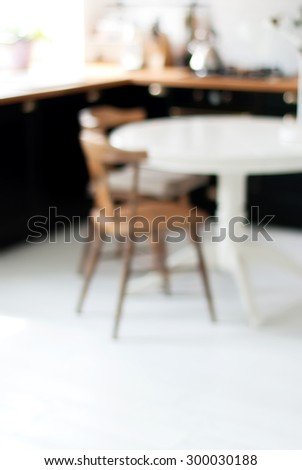 Blurred Background of Black, White Home Kitchen with Light Bokeh. Table and Chair on White Floor - stock photo