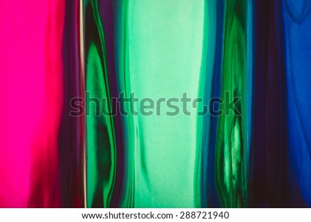 blurred background of colored glass, pink, blue and green glass macro background - stock photo