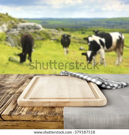 blurred background of cows on grass and shabby table of brown color and desk of kitchen  - stock photo