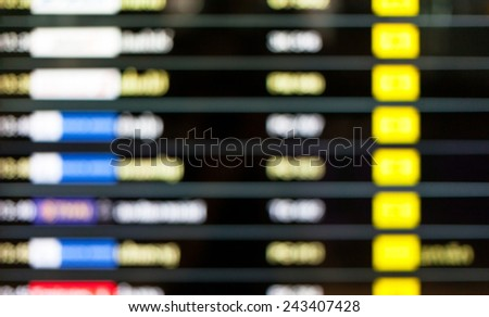 Blurred background of display schedule board in an airport with departure and arrival times. - stock photo