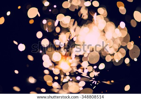 Blurred background of glowing sparks in the dark - stock photo