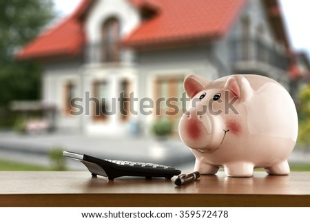blurred background of home and money in pig  - stock photo