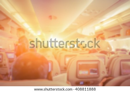 Blurred background of  interior aircraft , flight attendant helping passenger to put luggage cabin compartment.in vintage color effect. - stock photo